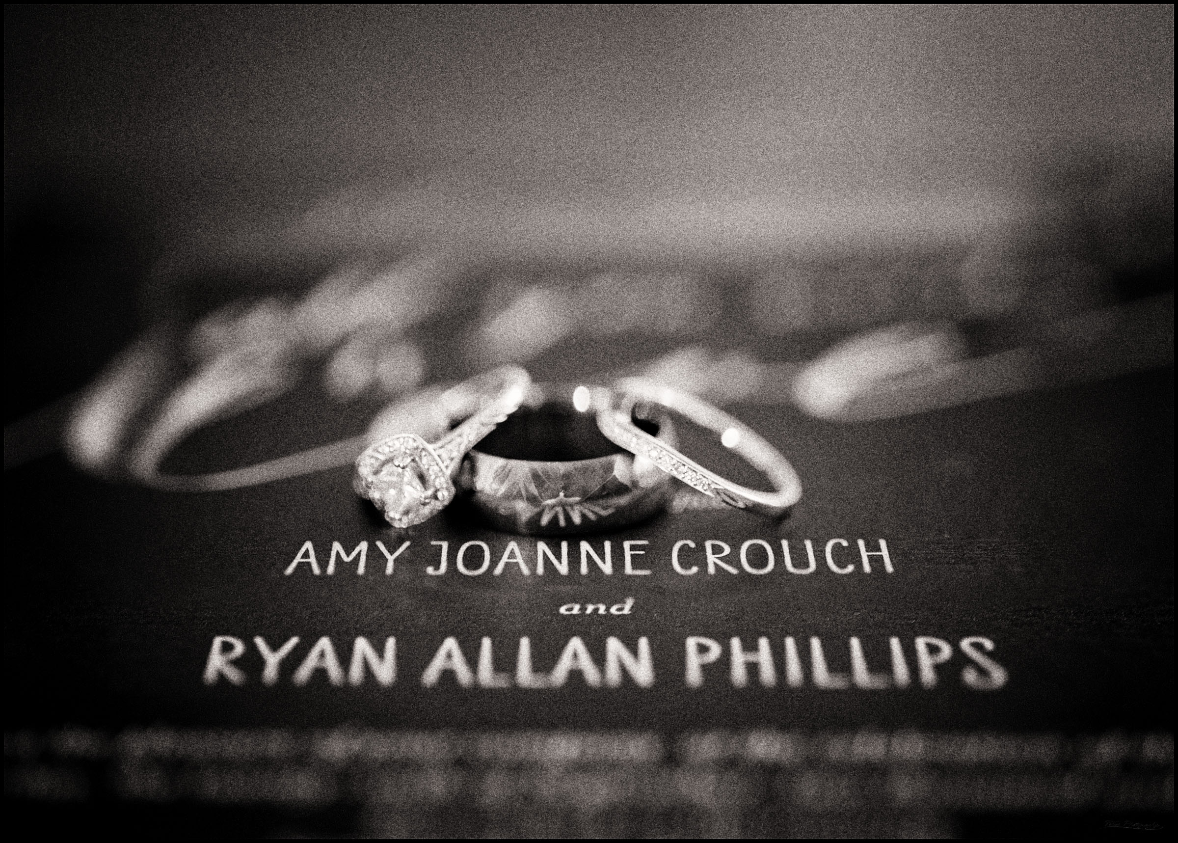 Wedding rings on invitation with reflection of couple