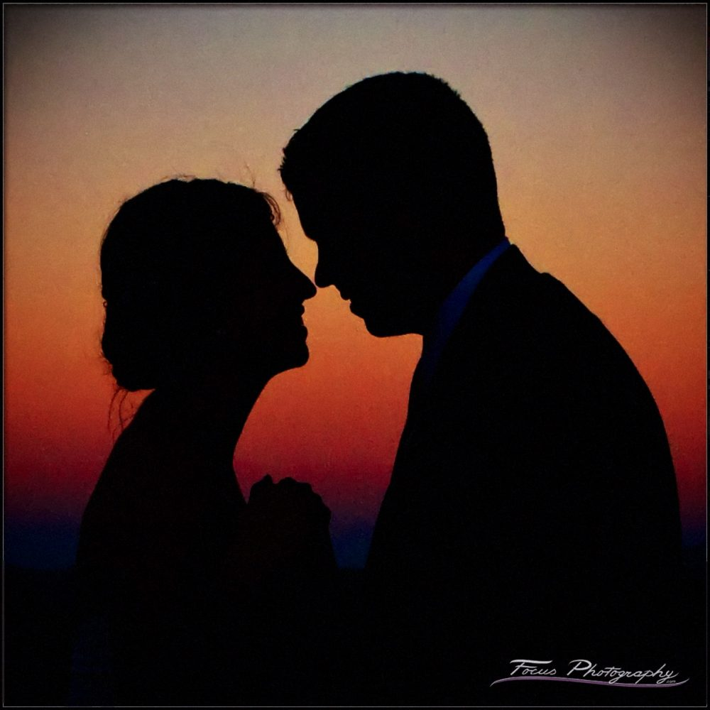 a sunset silhouette shot of a bride and groom at a sunday river wedding. Photography by Focus