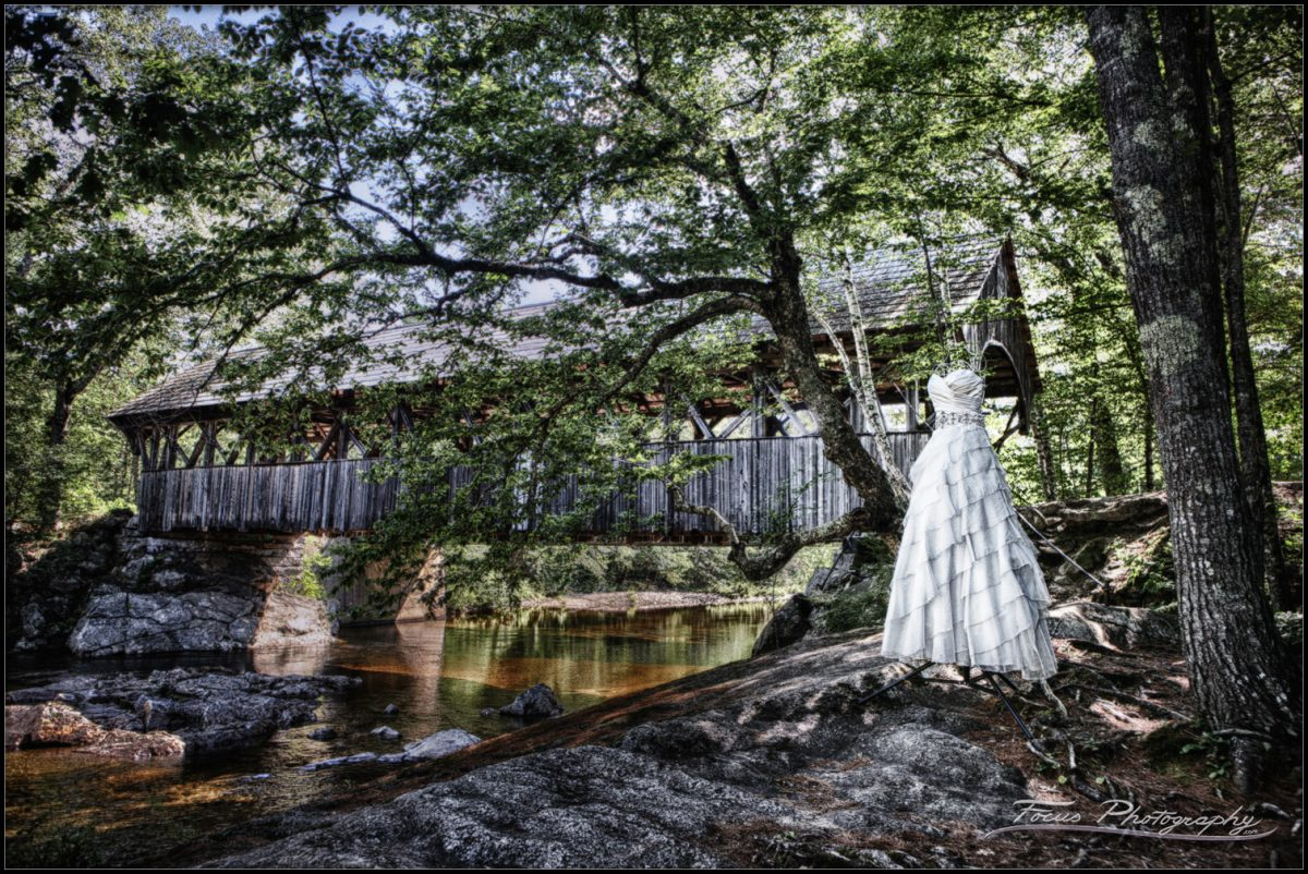 The wedding dress photographed at the artists' bridge in newry, maine for a sunday river wedding