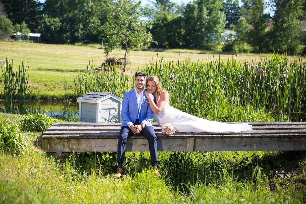 wedding couple at river winds farm wedding on bridge by pond