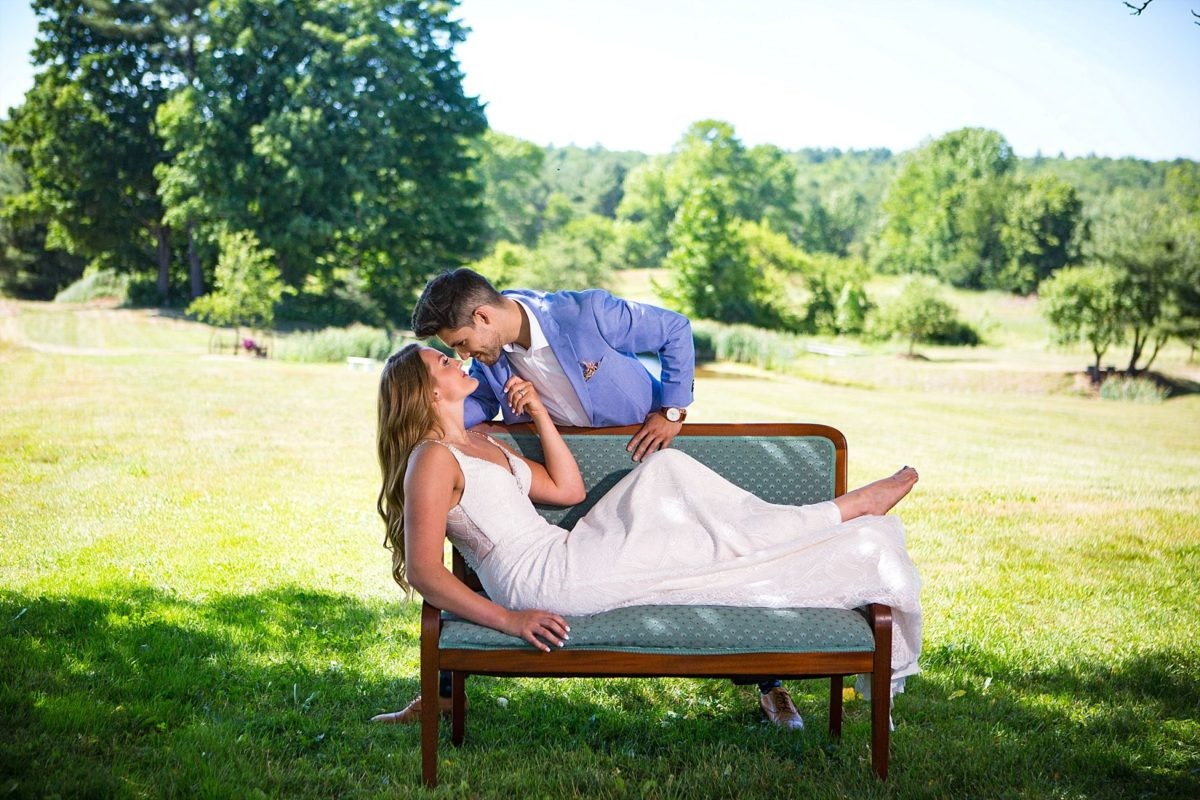 bride on settee pulls groom close at river winds farm