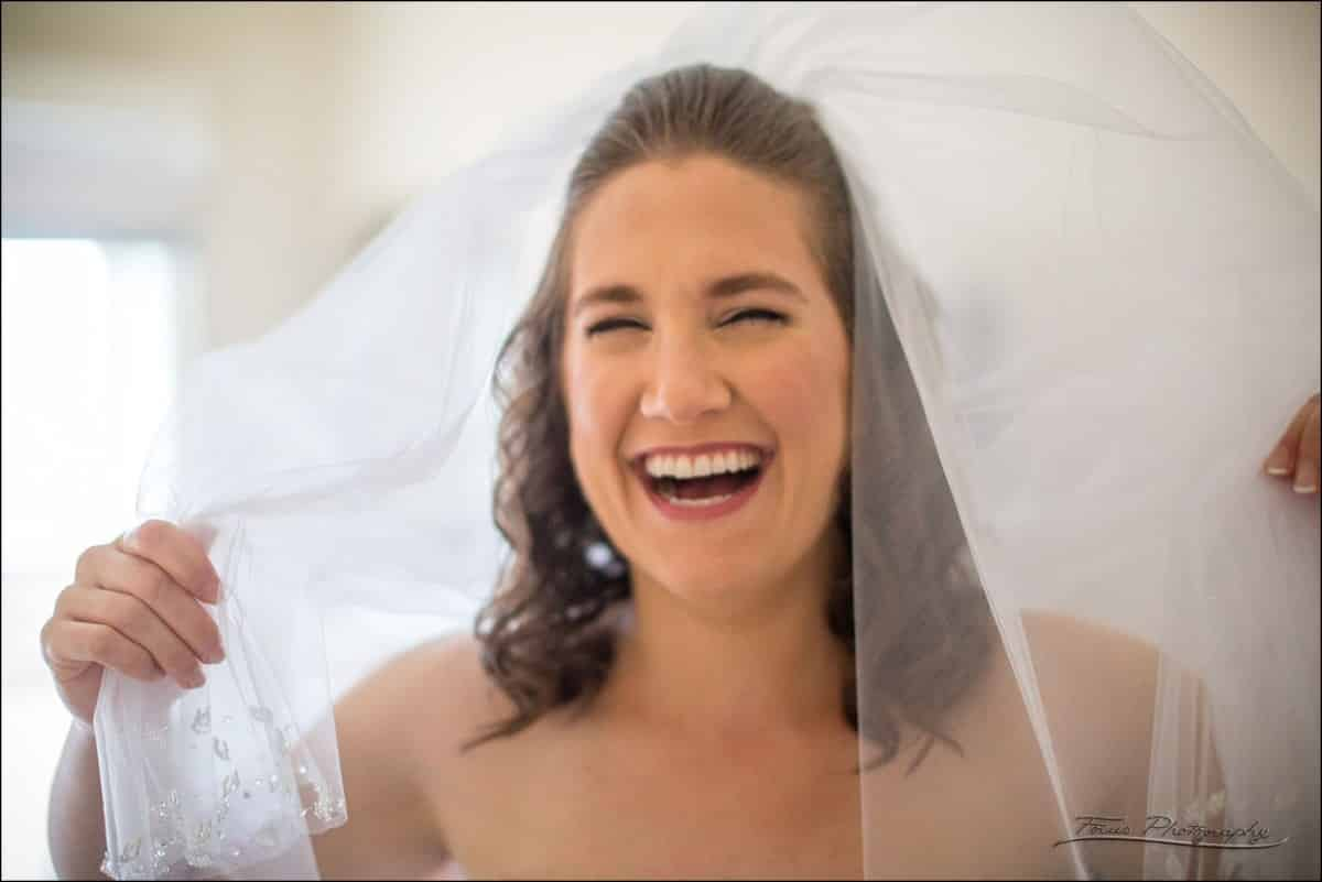 bride laughing under veil at Wentworth by the Sea wedding