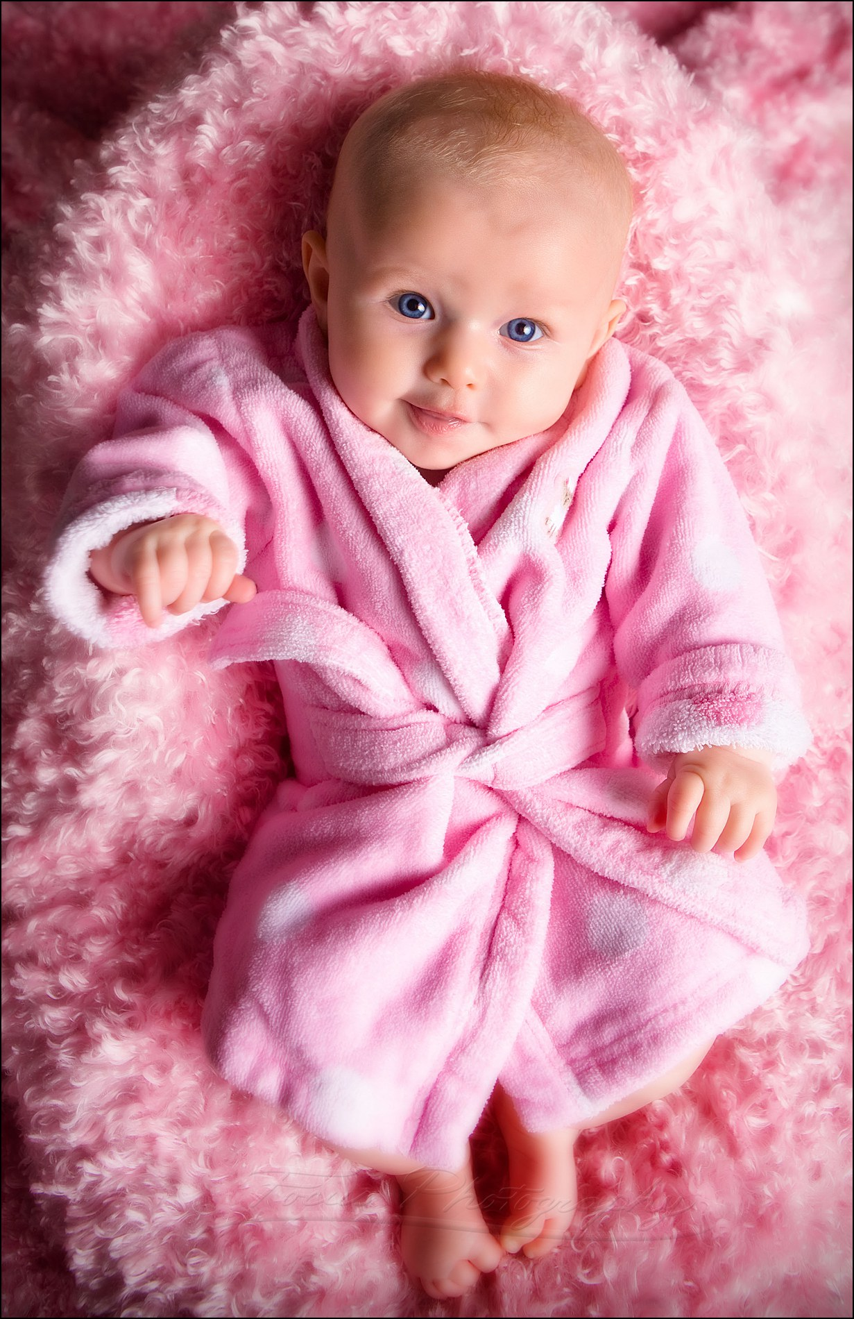newborn baby girl in pink robe photographed looking up to the camera