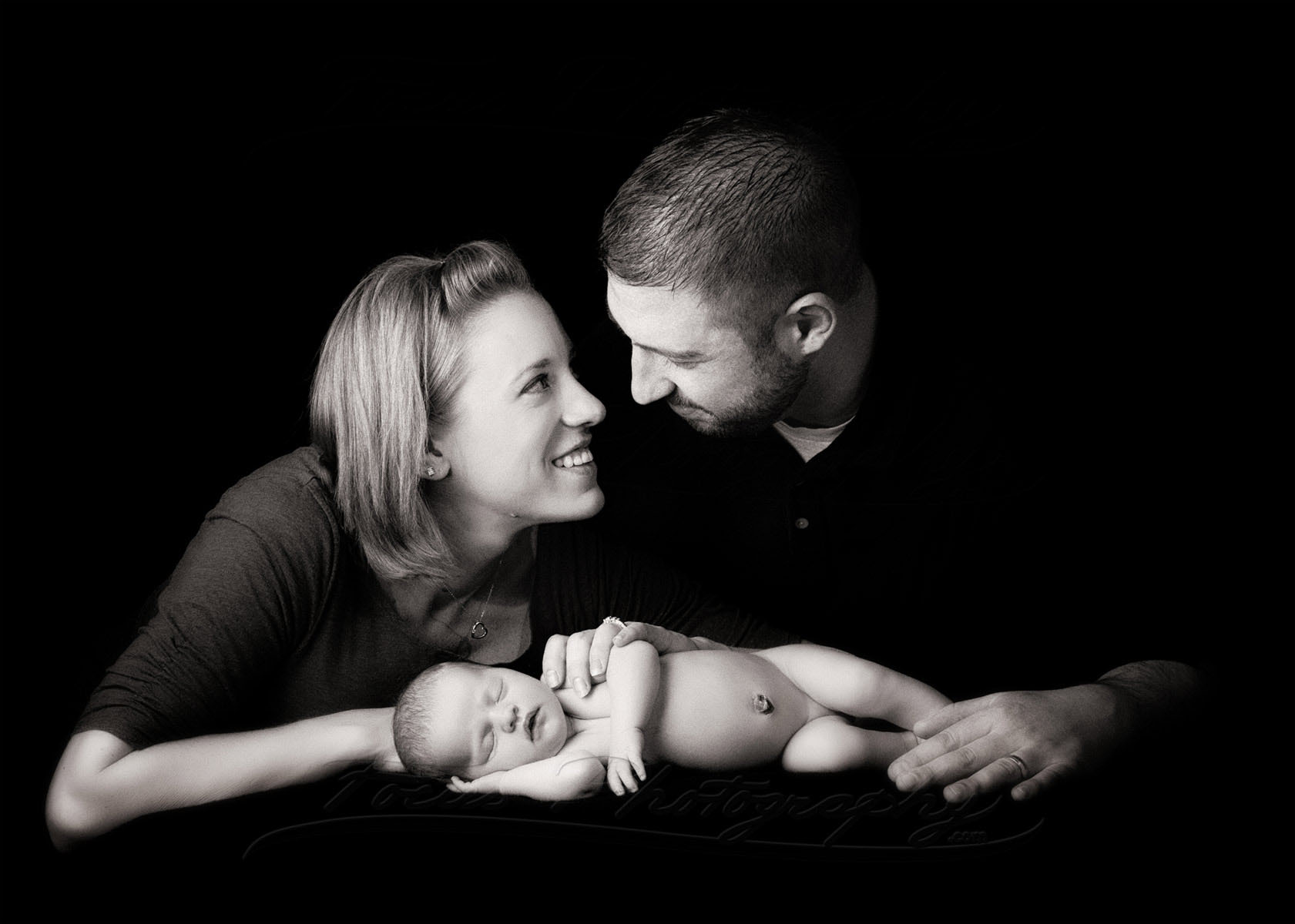low key family photo of parents with new baby