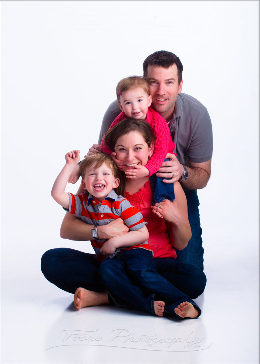 fun family picture with 2 small kids on white background in maine photography studio