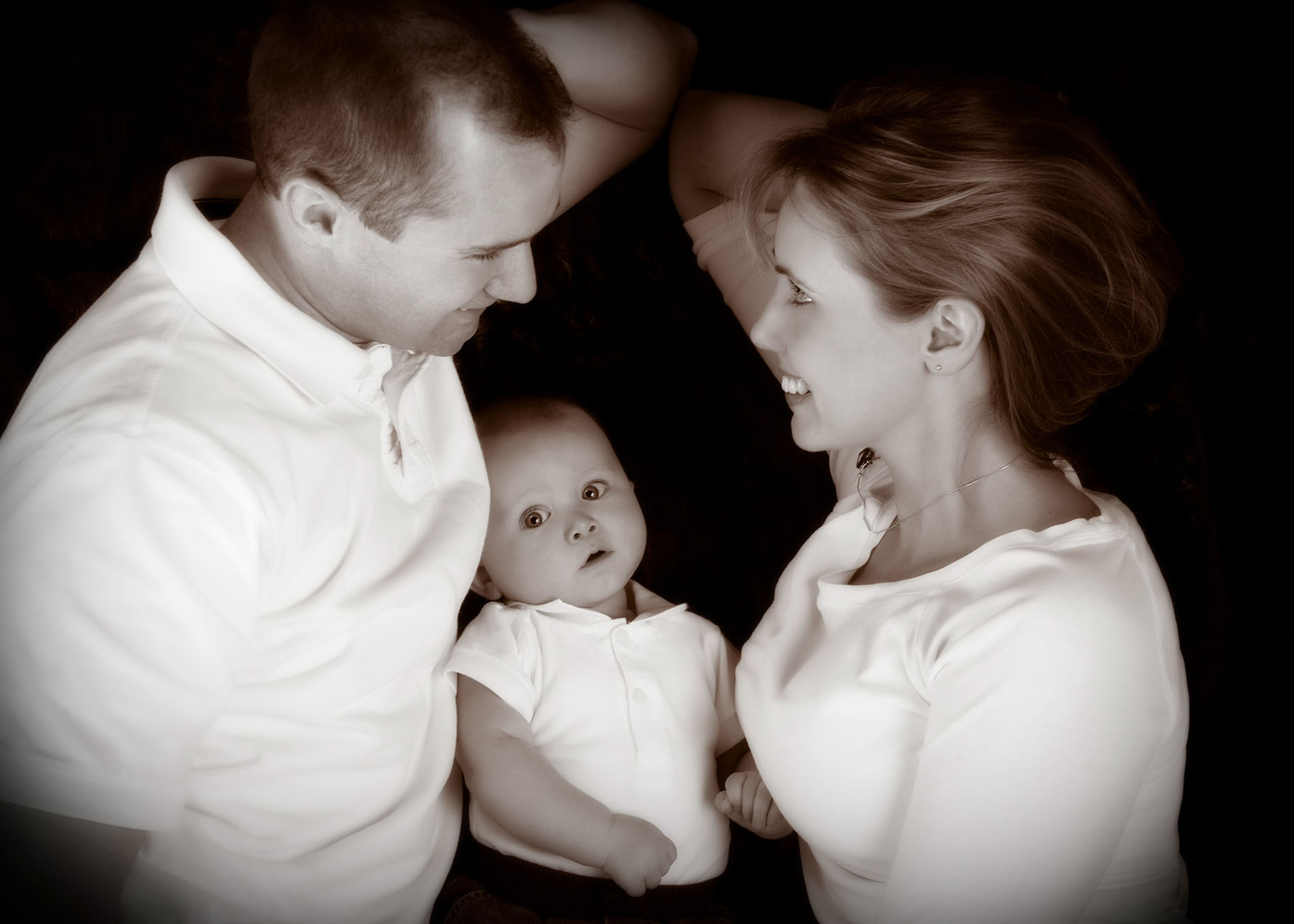 parents look at each other while baby looks at camera in black and white photo