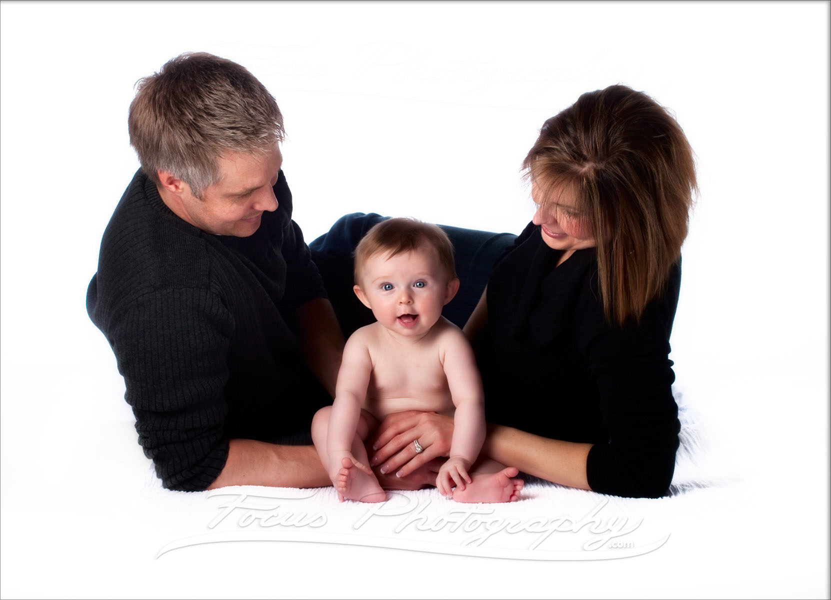 baby with big eyes looks at camera while parents look at baby in portrait on white in Maine family photo studio