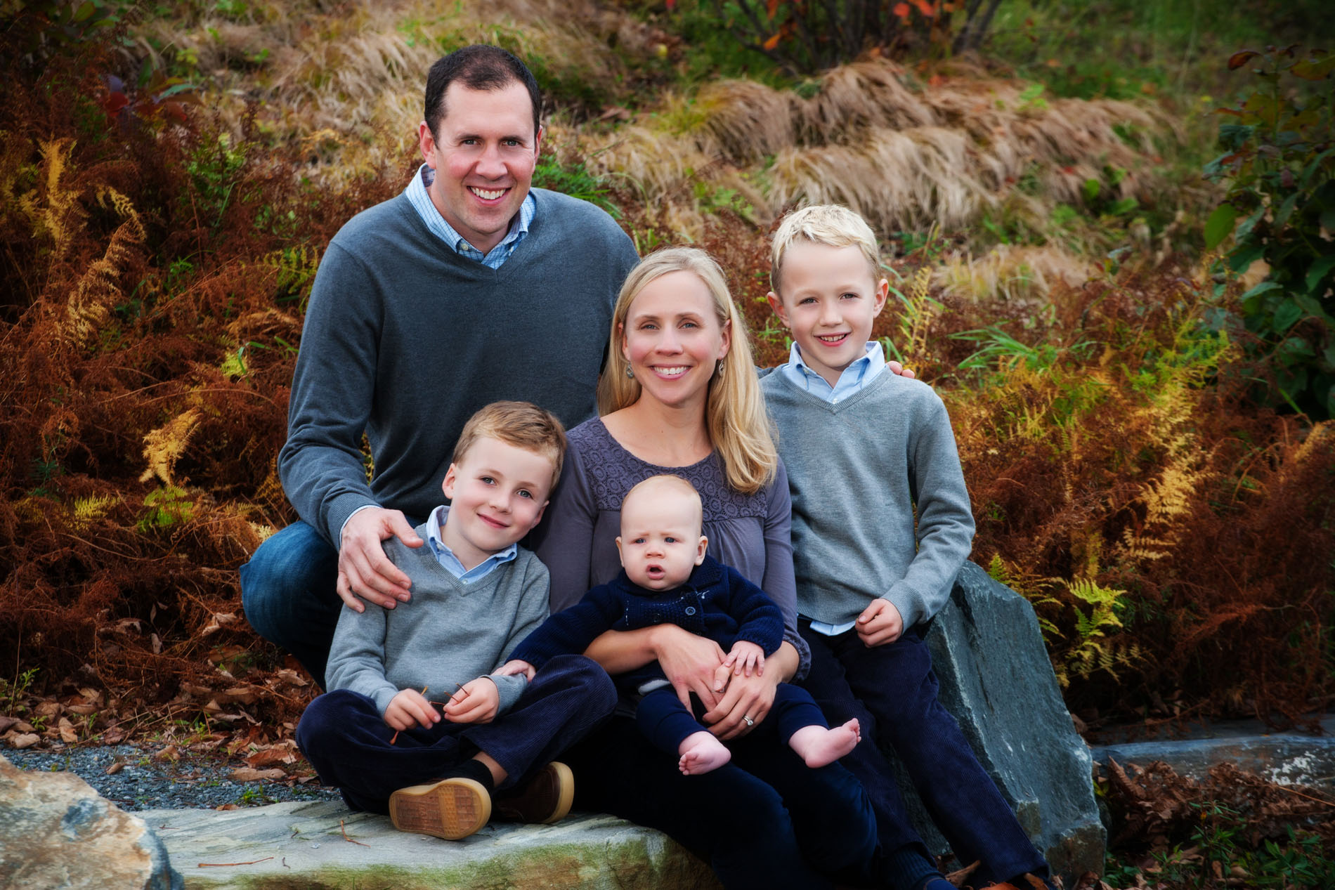 young family photographed at the park in maine with new baby