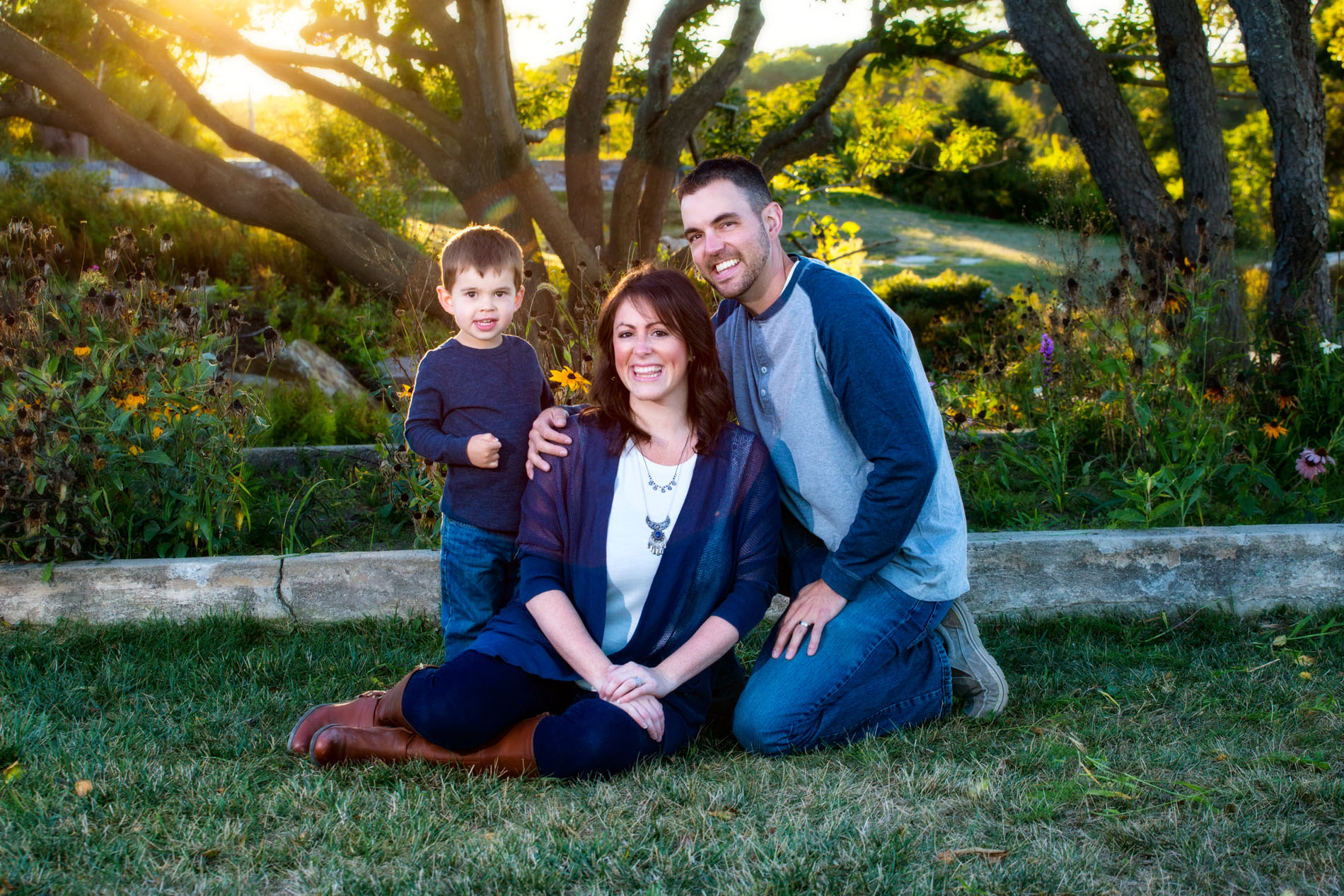 mom surrounded by dad and young son for fun outdoor family picture