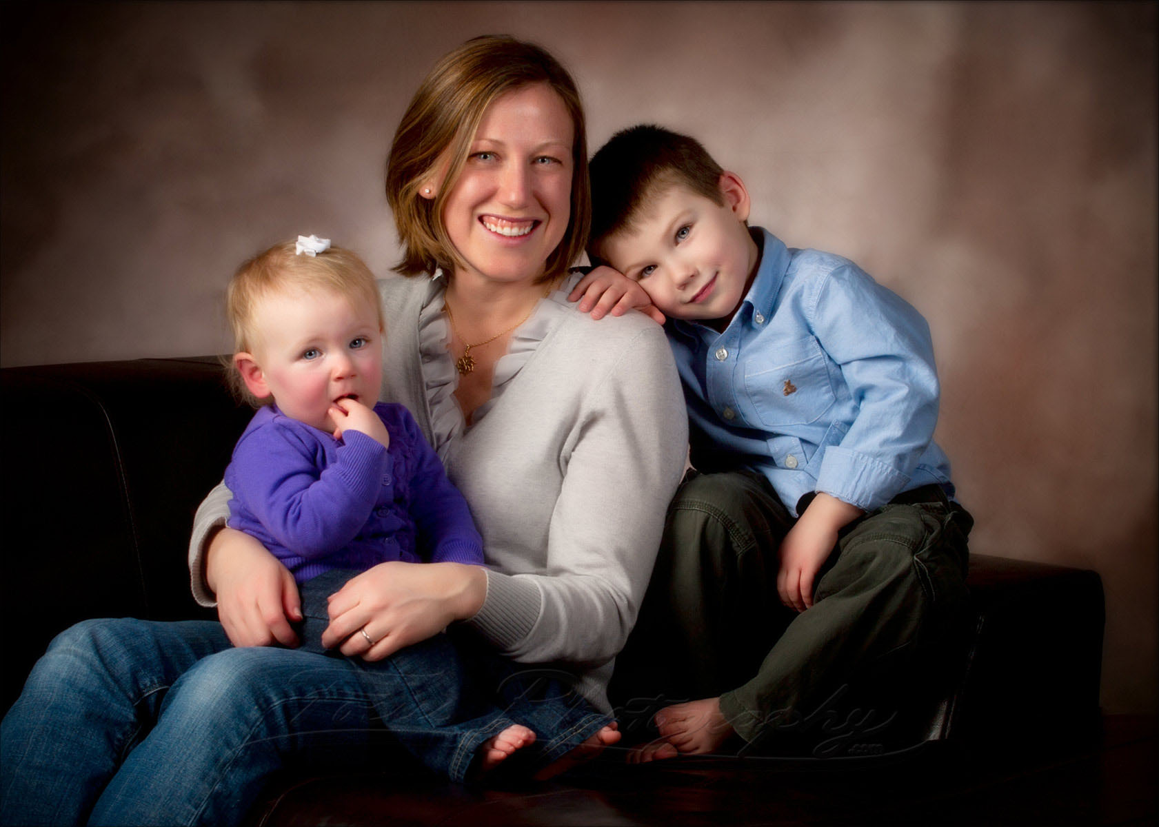 mom and her young boy seated with new baby sister for portrait
