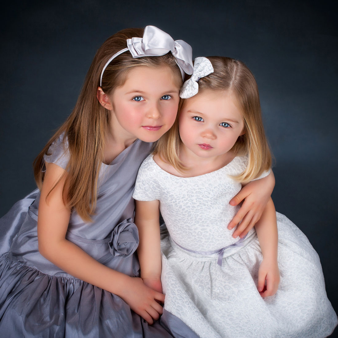 little girls looking up at camera in kids' picture at family portrait studio
