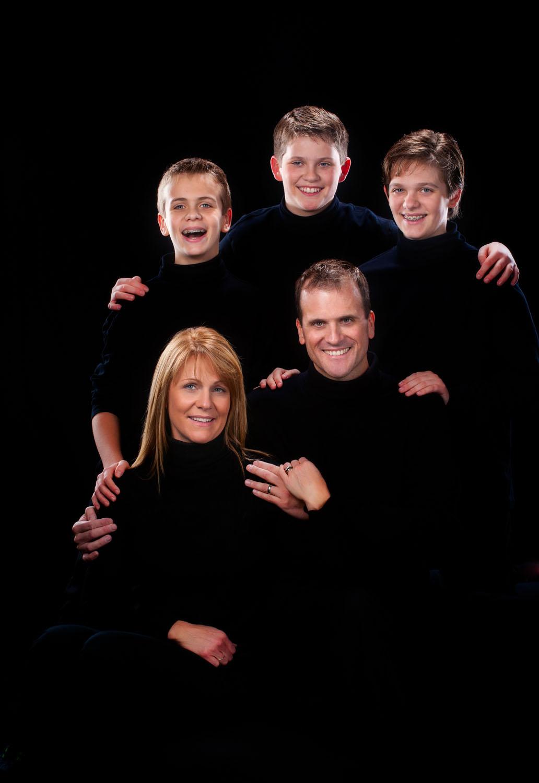 emotive low key portrait of family on black