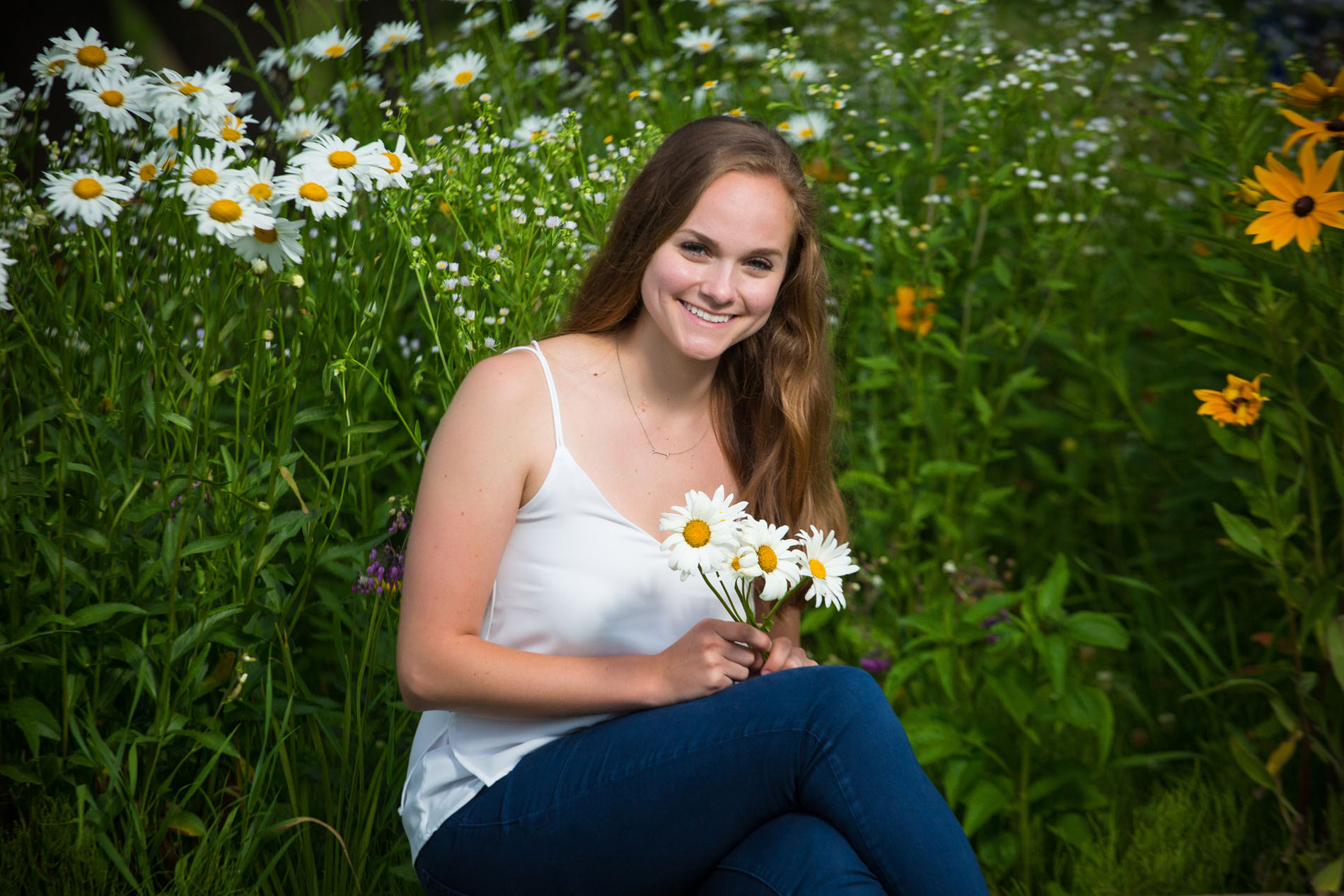 girl in white tank top photographed among sun flowers in fort williams park for senior photo shoot