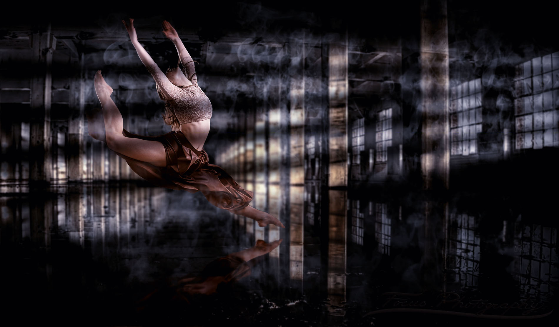 dancer leaps over water in warehouse but photographed in senior photography studio