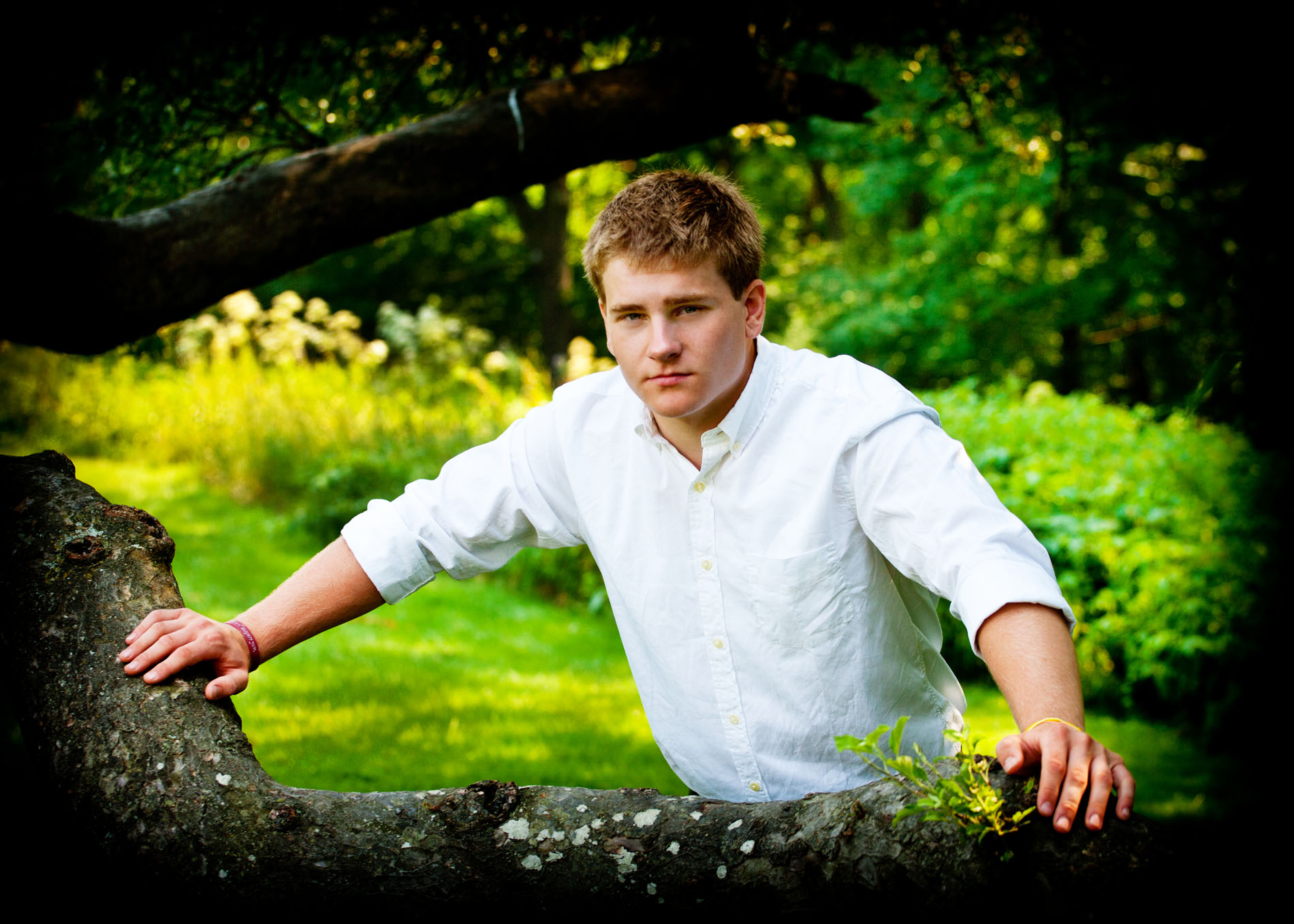 senior guy leaning on tree at audubon center in falmouth, maine for photo shoot
