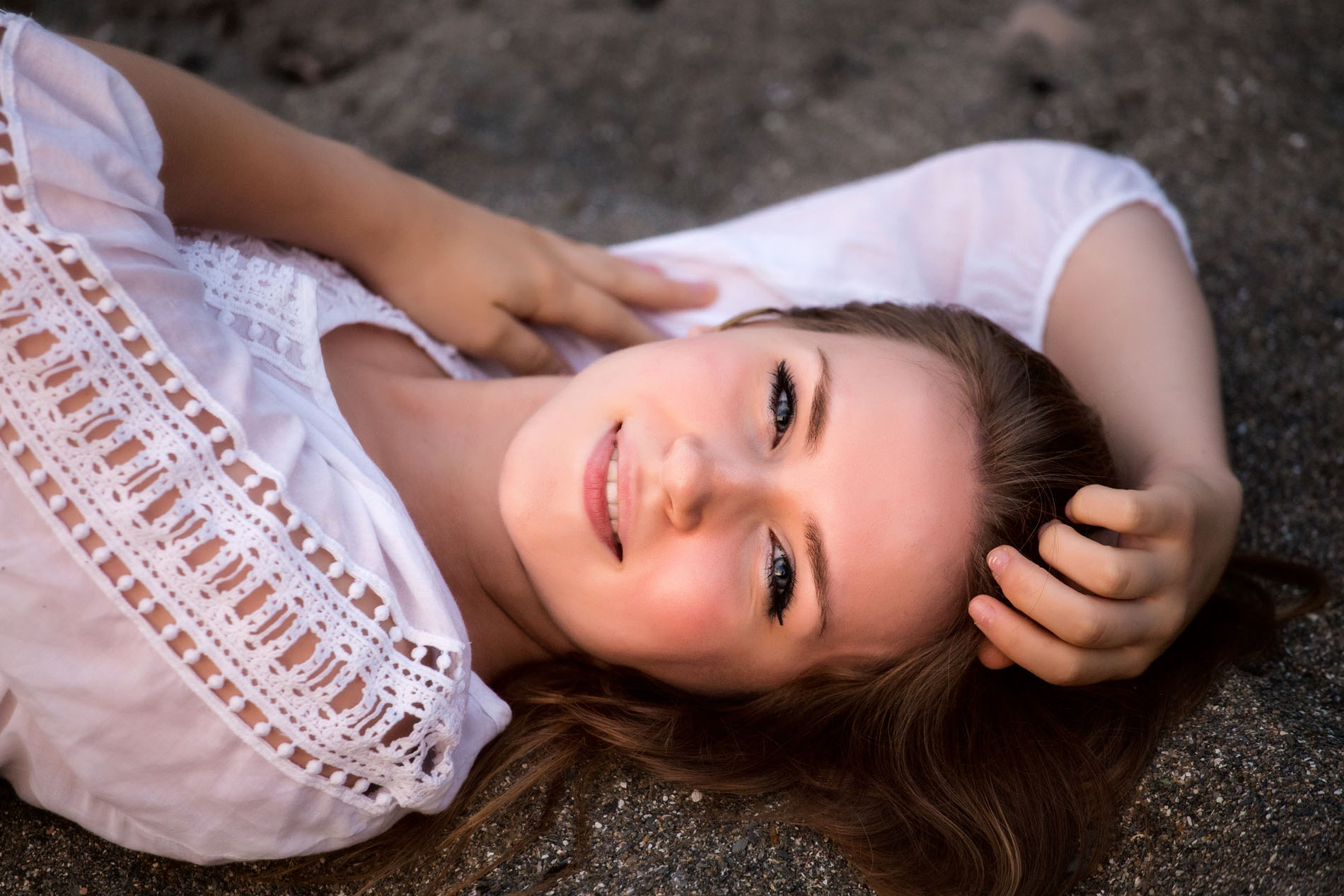 senior girl photographed at beach in maine for graduation pictures lays on sand looking up