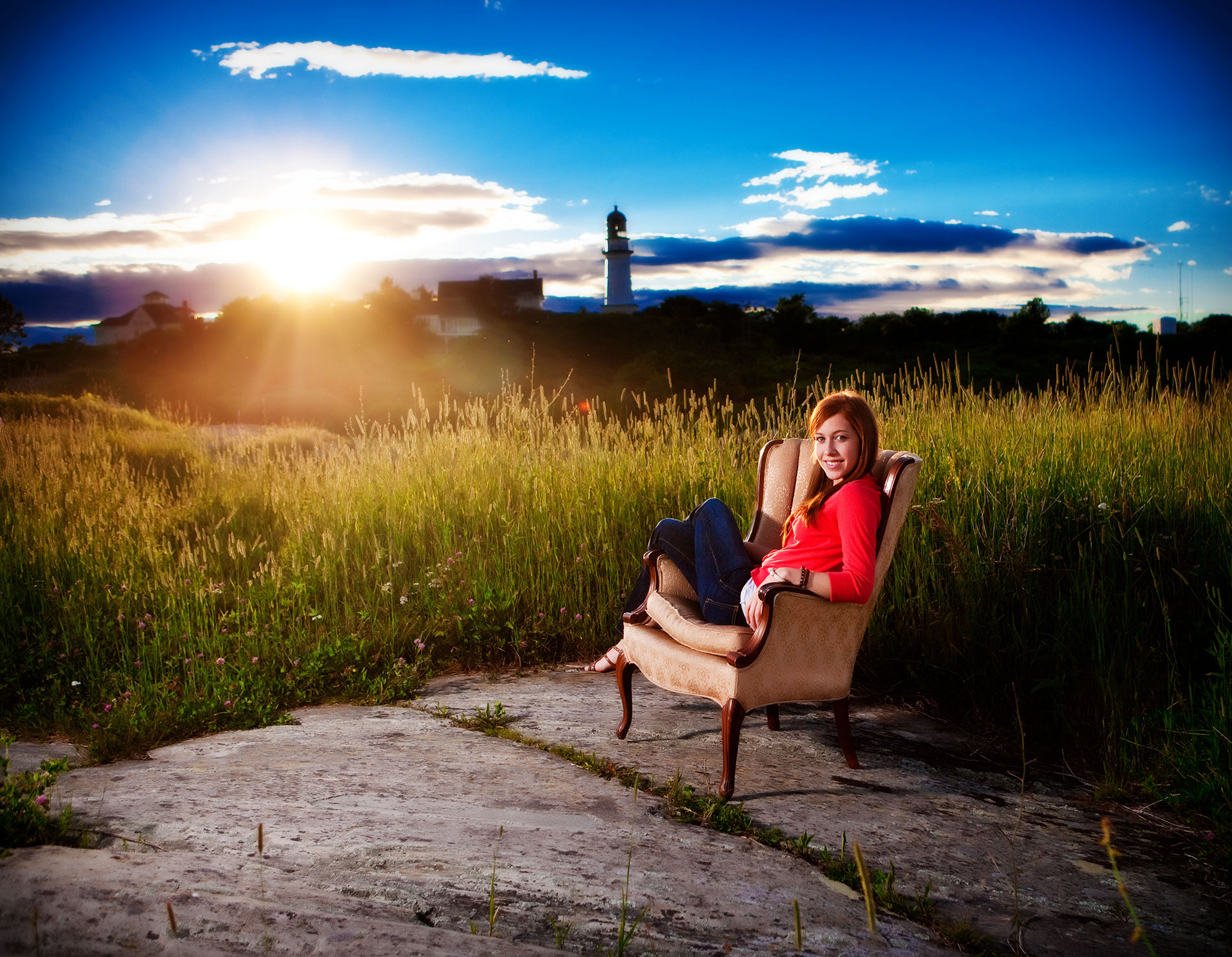 cool senior picture of girl in chair with lighthouse behind her