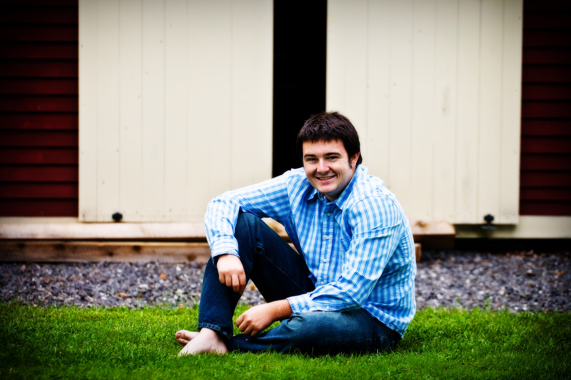 senior guy photographed with barn at his house