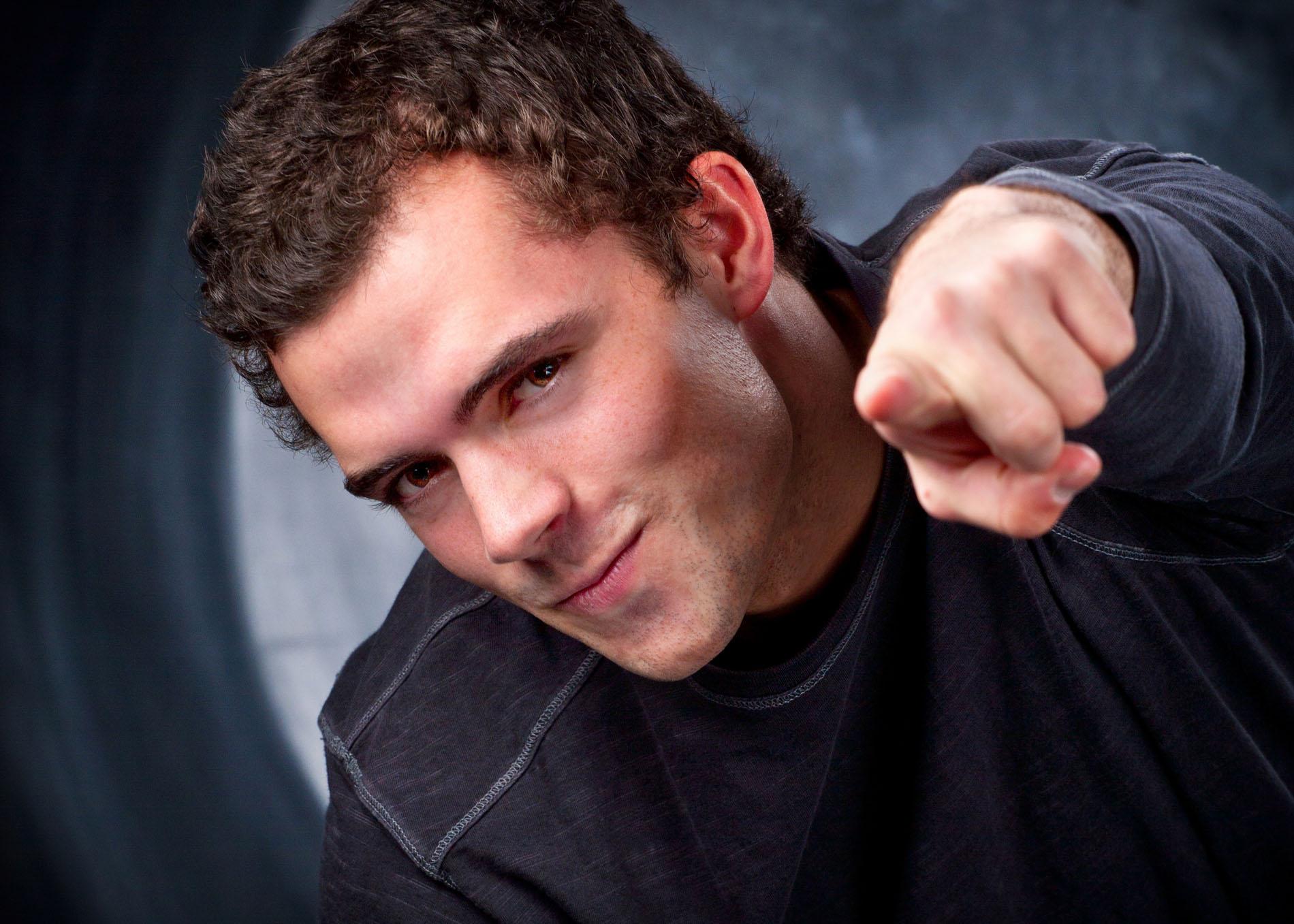 senior guy pointing at lens in studio portrait