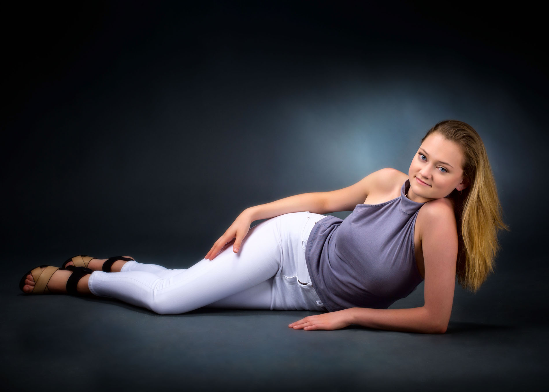 girl wearing white pants and gray top lying on ground for senior photo in studio