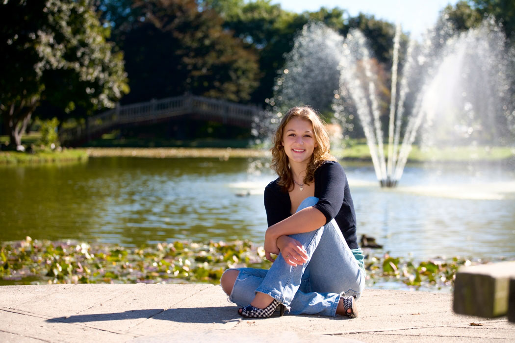 girl with houndstooth shoes poses by fountain in park for senior portraits
