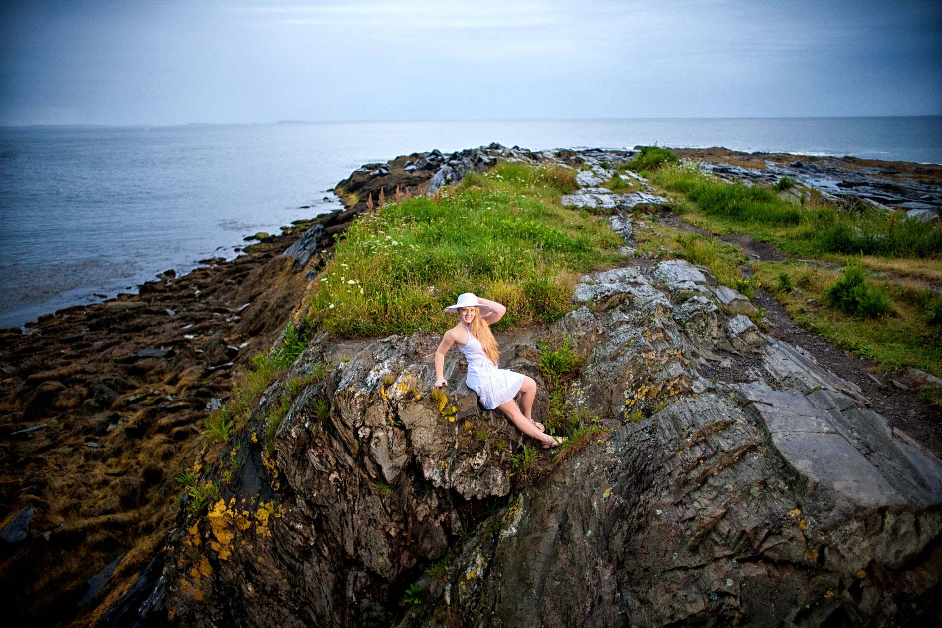 girl with white hat on rocks on cliff at shore in cape elizabeth for senior portrait