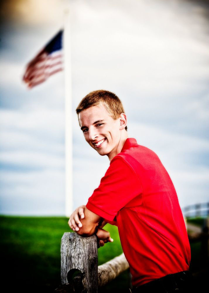 senior picture of boy in red shirt in front of american flag taken at park