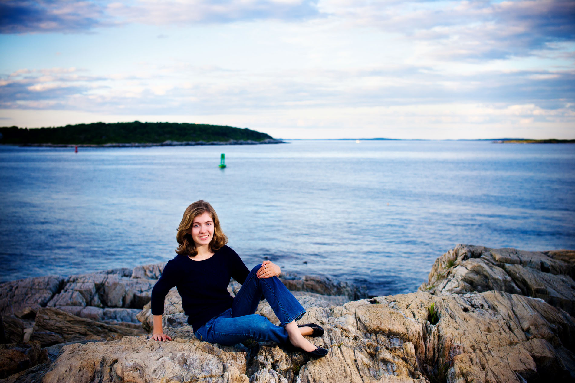 senior girl on rocks in front of ocean in fort williams park in maien