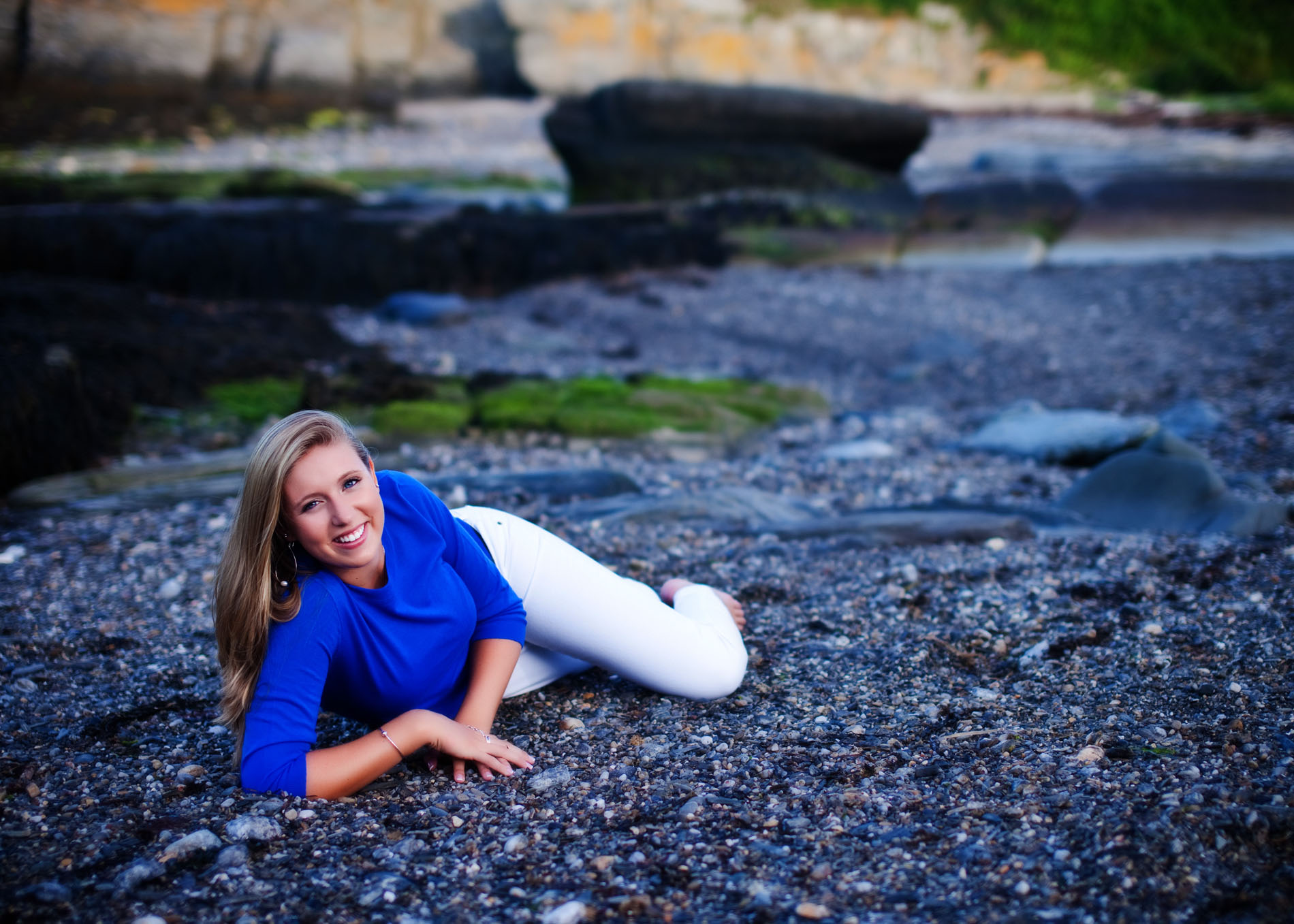 senior photo of girl in blue shirt laying on rocky beach in maine