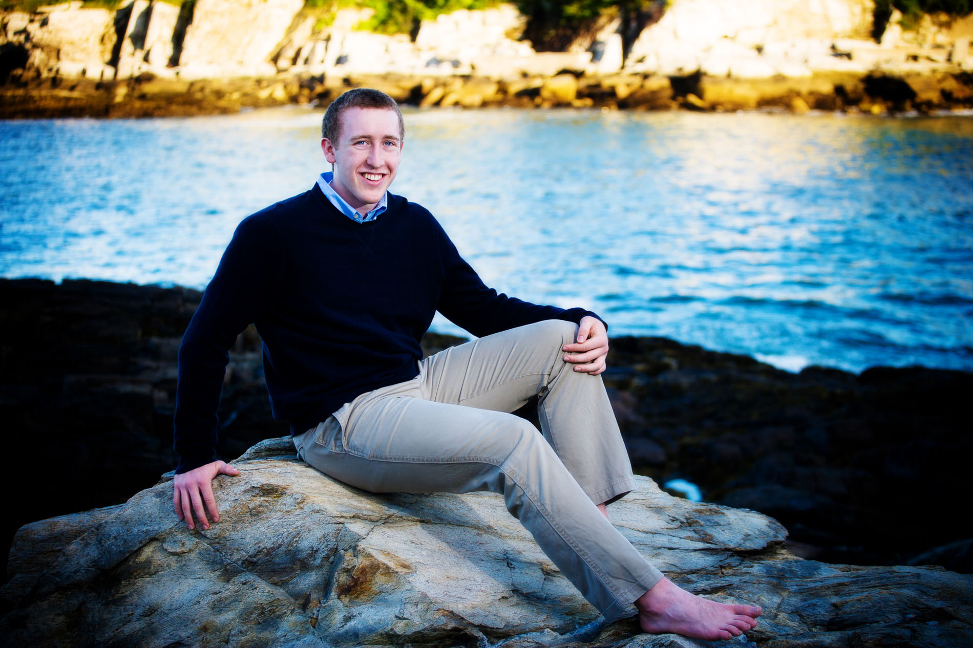 senior boy barefoot on rocks by water in fort williams