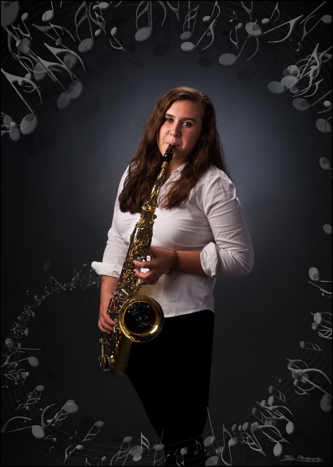 musician playing saxophone with notes flying out of it for senior photo in studio