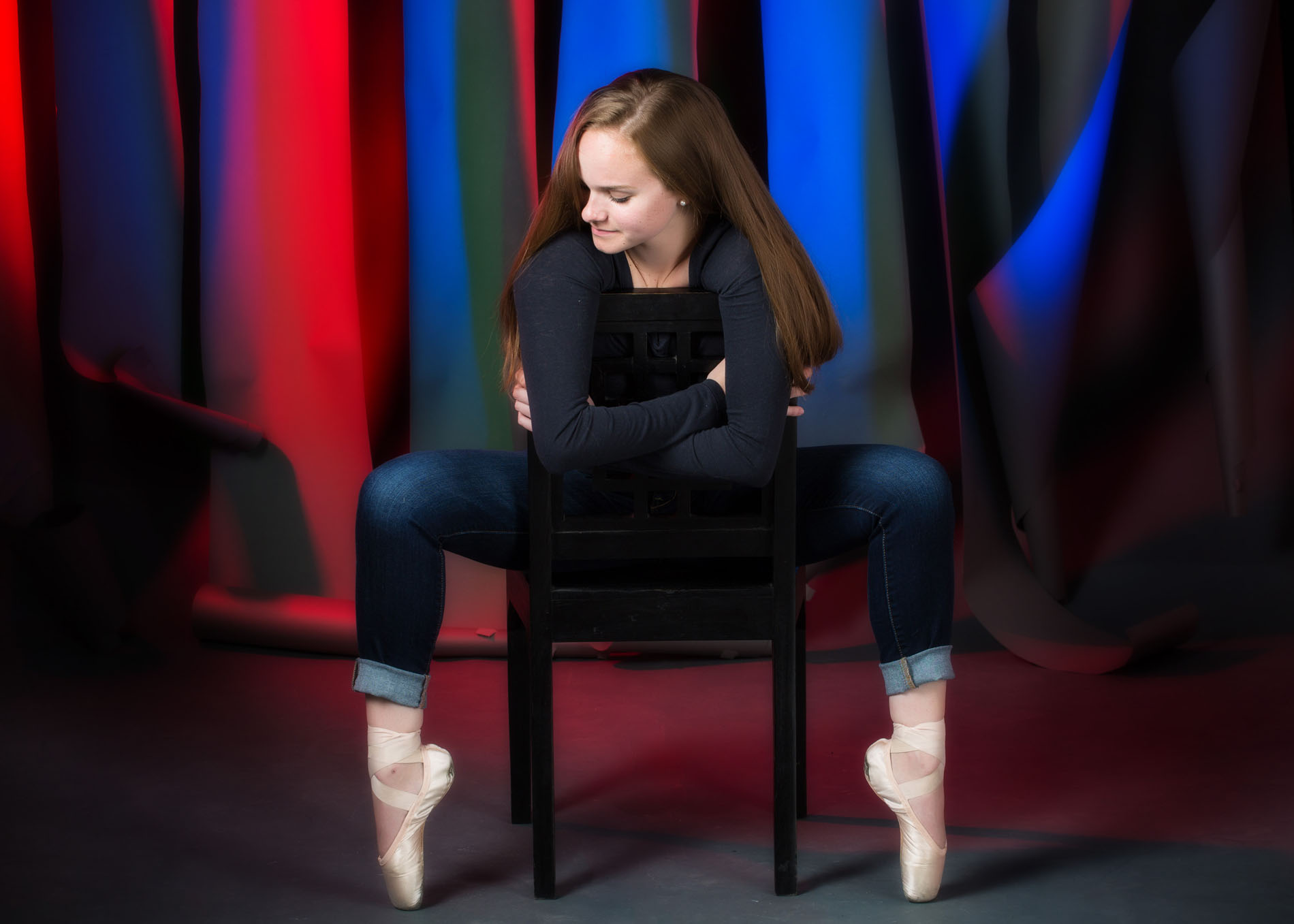 dancer wearing tap shoes photographed in studio with blue and red lights shining on background
