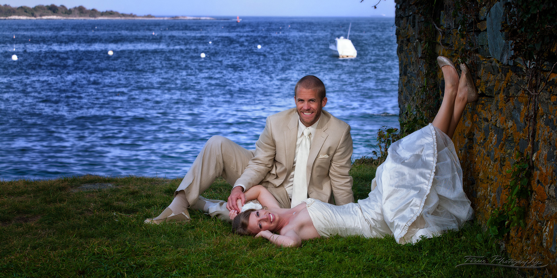 Bride laying against rocks with groom at Willard Beach in South Portland, Maine