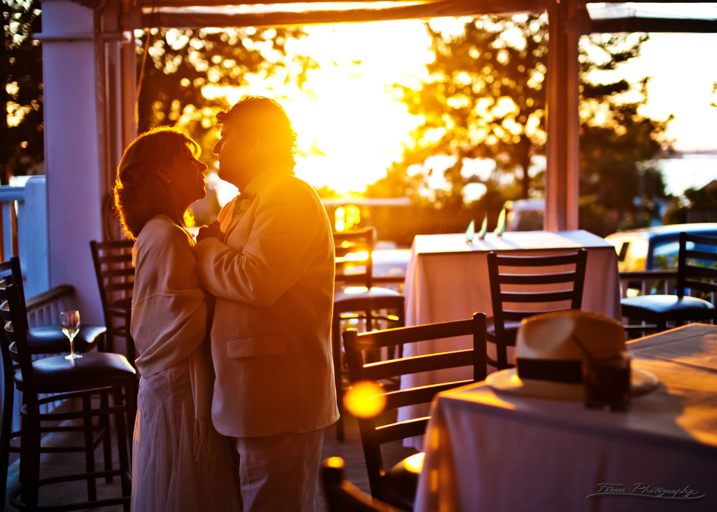 Bride and groom embracing each other at reception with sunset