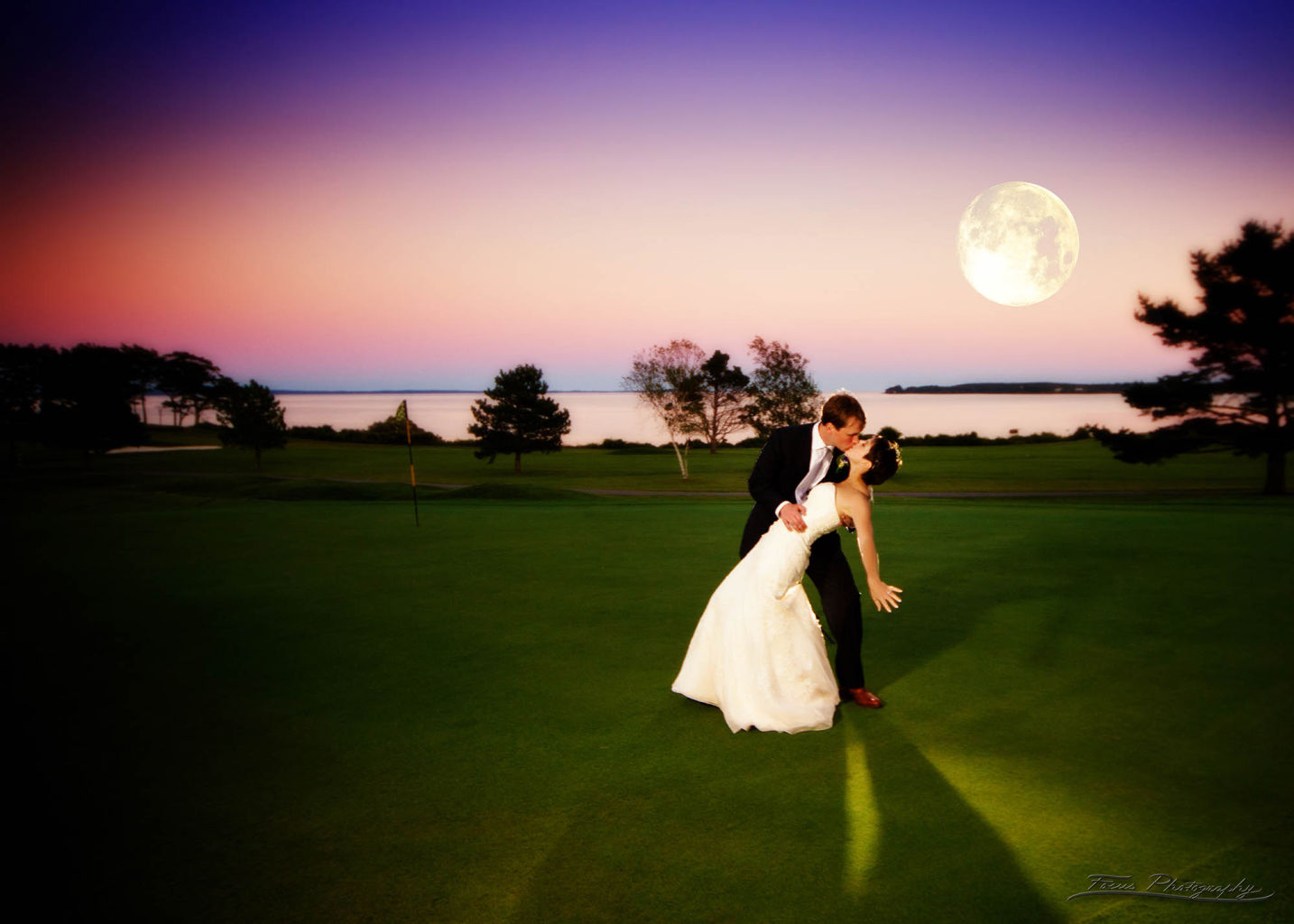 The bride and groom dance in the moonlight at the Samoset Resort