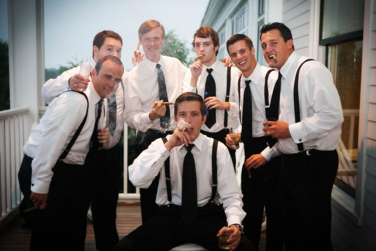 the men smoke cigars during the wedding reception at the Wentworth by the Sea