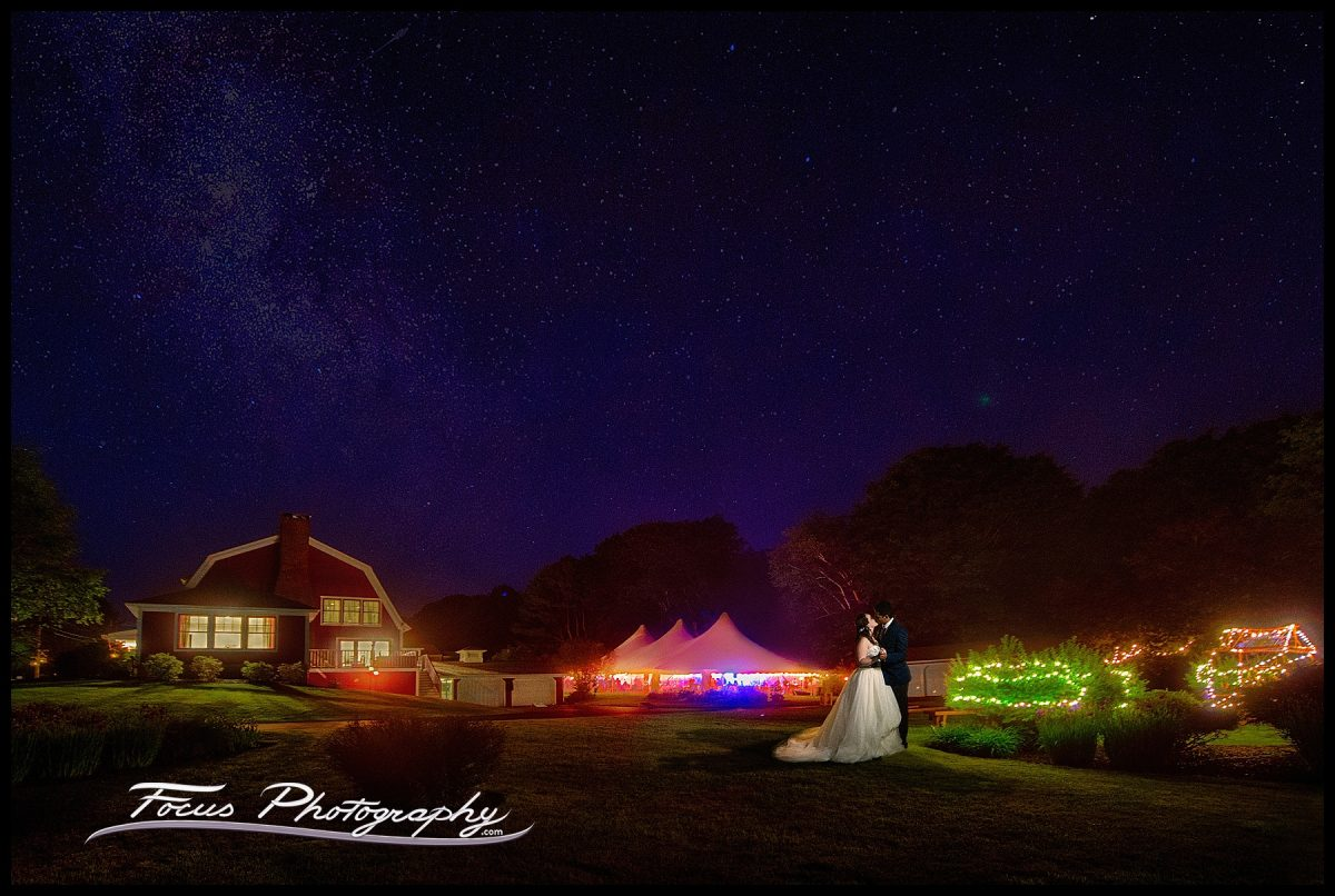 Night photography of bride and groom in front of backyard wedding and tent in Falmouth Foreside, Maine wedding. Photographers Will and Lucia of Focus Photography